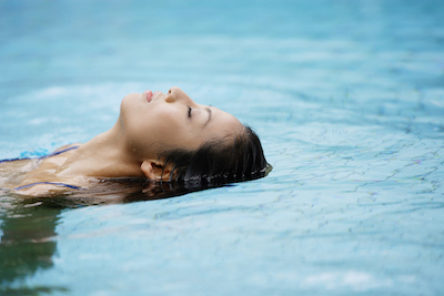 Relaxed looking lady floating in a pool