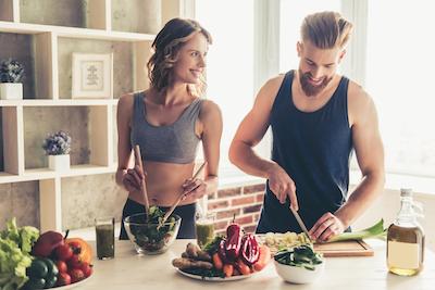 Happy healthy looking couple preparing a healthy meal