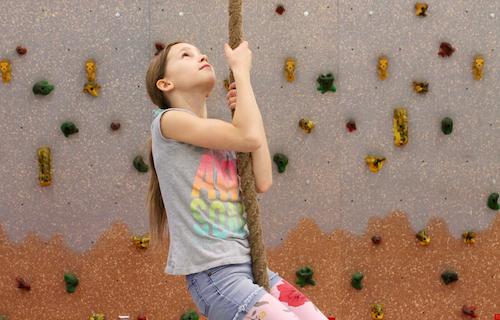 Girl climbing rope in a PE class