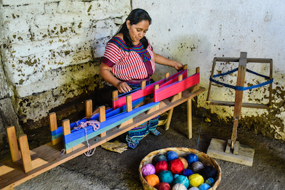 Woman weaving cotton dyed with vegetable extracts